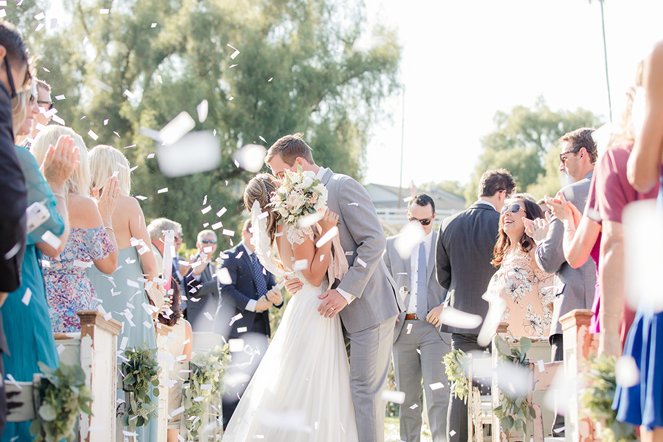 Rancho palos verdes outdoor wedding at a private estate bride a line chiffon gown with a lace bodice and short lace sleeves with a sweetheart neckline and groom heather grey notch lapel suit with a matching vest and white dress shirt with a long white tie kissing after ceremony in aisle with white confetti bride holding white and green floral bridal bouquet