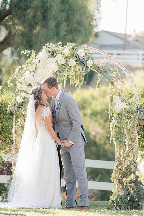 Rancho palos verdes outdoor wedding at a private estate bride a line chiffon gown with a lace bodice and short lace sleeves with a sweetheart neckline and groom heather grey notch lapel suit with a matching vest and white dress shirt with a long white tie holding hands and kissing during ceremony