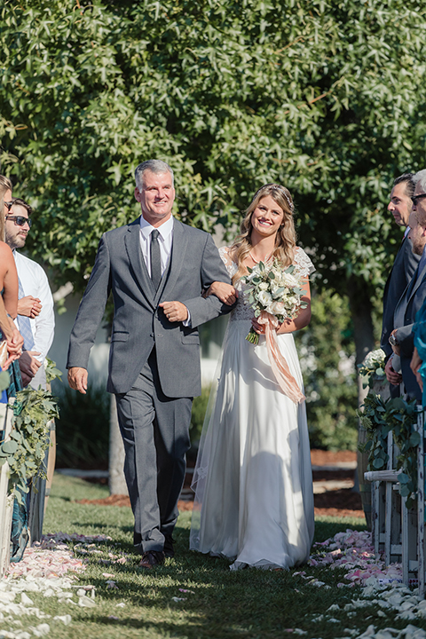 Rancho palos verdes outdoor wedding at a private estate bride a line chiffon gown with a lace bodice and short lace sleeves with a sweetheart neckline holding white and green floral bridal bouquet walking down the aisle with dad charcoal suit holding white and green floral bridal bouquet
