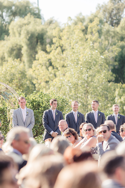 Rancho palos verdes outdoor wedding at a private estate wedding ceremony groom heather grey notch lapel suit with a matching vest and white dress shirt with a long white tie watching bride walk down the aisle with groomsmen charcoal grey suits with long white ties