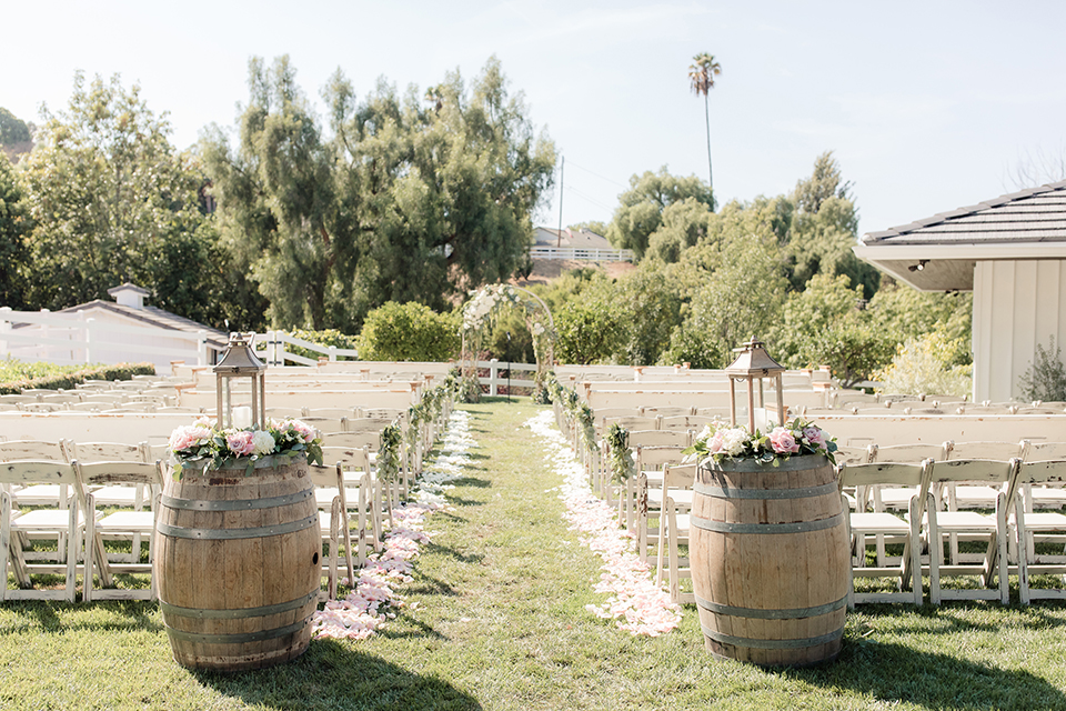 Rancho palos verdes outdoor wedding at a private estate wedding ceremony set up with white chairs and white and green flowers on altar and white petals along aisle with two wine barrels at entrance with lantern and candle decor wedding photo idea for ceremony set up