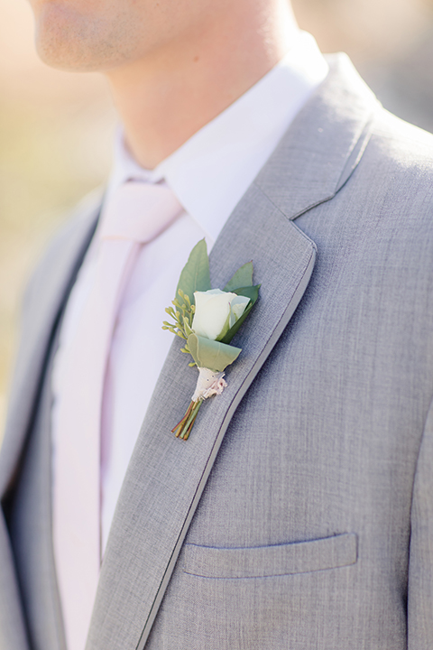 Rancho palos verdes outdoor wedding at a private estate groom heather grey notch lapel suit with a matching vest and white dress shirt with a long white tie and white floral boutonniere close up
