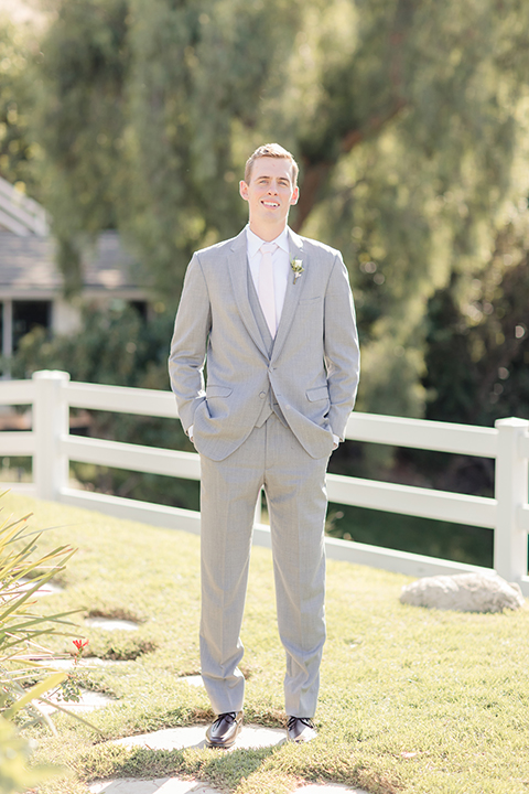 Rancho palos verdes outdoor wedding at a private estate groom heather grey notch lapel suit with a matching vest and white dress shirt with a long white tie and white floral boutonniere standing with hands in pockets