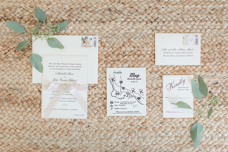 Rancho palos verdes outdoor wedding at a private estate wedding invitations white with small cursive writing and green floral decor on tan wicker background decor with envelope wedding photo idea for invitations