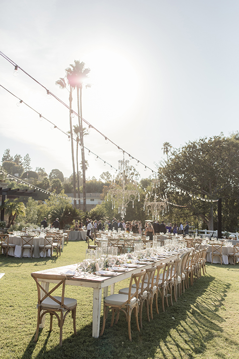 Rancho palos verdes outdoor wedding at a private estate reception set up with grey table linens and white place settings with white napkins and green floral centerpiece decor with glass vases and floating white candles with brown wood chairs and hanging light decor