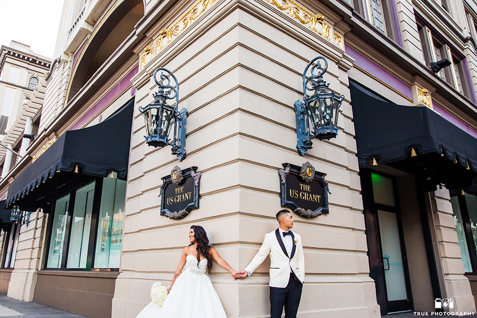 San diego glamorous wedding at the us grant hotel bride strapless ball gown with a tulle skirt and sweetheart neckline and a crystal belt with a long veil and groom white tuxedo jacket with a black shawl and black pants with a black bow tie and white floral boutonniere holding hands outside hotel