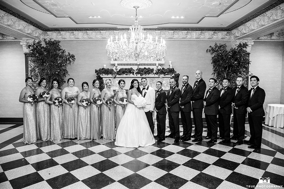 San diego glamorous wedding at the us grant hotel bride strapless ball gown with a tulle skirt and sweetheart neckline and a crystal belt with a long veil and groom white tuxedo jacket with a black shawl and black pants with a black bow tie and white floral boutonniere with wedding party bridesmaids long gold dresses with red floral bouquets and groomsmen black tuxedos with black bow ties