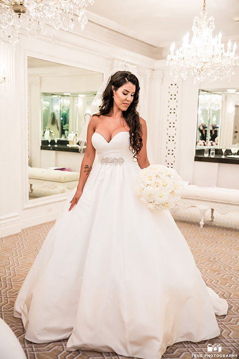 San diego glamorous wedding at the us grant hotel bride strapless ball gown with a tulle skirt and sweetheart neckline and a crystal belt with a long veil holding white floral bridal bouquet