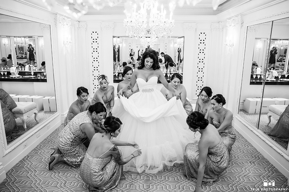 San diego glamorous wedding at the us grant hotel bride strapless ball gown with a tulle skirt and sweetheart neckline and a crystal belt with a long veil holding white floral bridal bouquet with bridesmaids getting ready gold dresses black and white photo