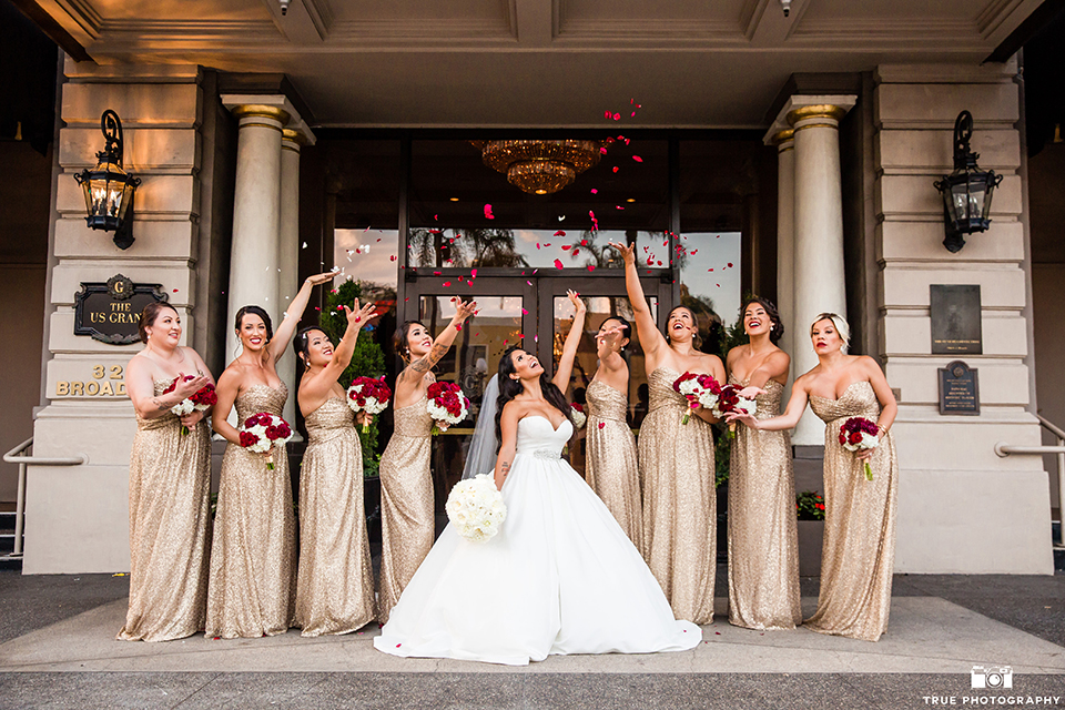 San diego glamorous wedding at the us grant hotel bride strapless ball gown with a tulle skirt and sweetheart neckline and a crystal belt with a long veil holding white floral bridal bouquet with bridesmaids long gold dresses and red floral bouquets cheering