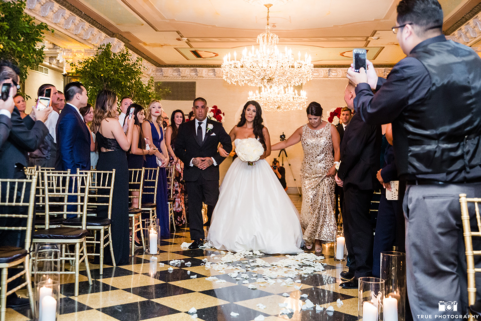 San diego glamorous wedding at the us grant hotel bride strapless ball gown with a tulle skirt and sweetheart neckline and a crystal belt with a long veil holding white floral bridal bouquet walking down the aisle with parents