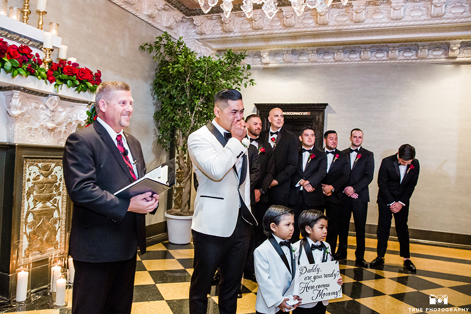 San diego glamorous wedding at the us grant hotel groom white tuxedo with black shawl lapel and black tuxedo pants with a white dress shirt and black bow tie with a white floral boutonniere crying watching bride walk down the aisle during ceremony