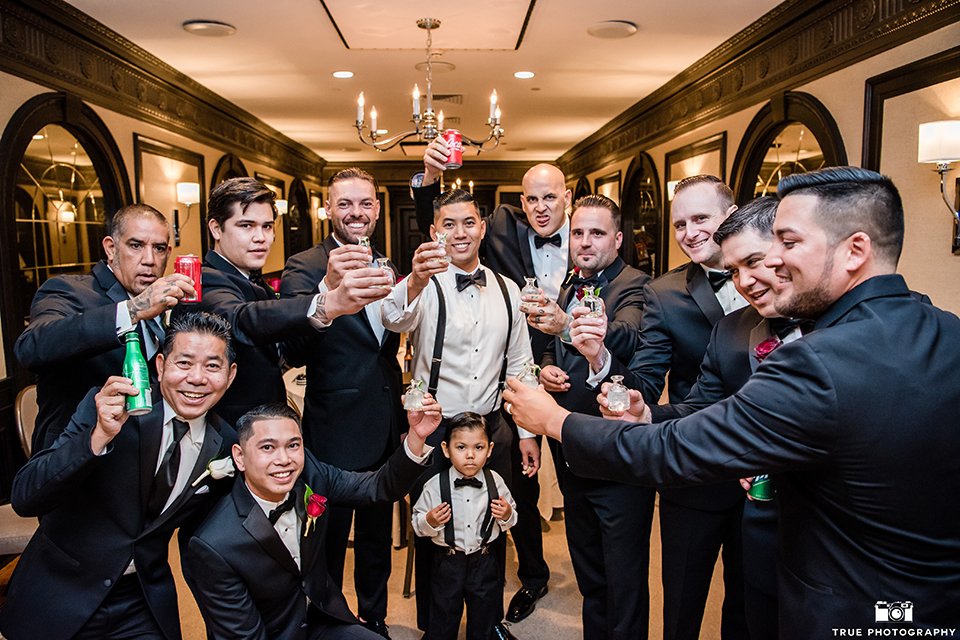San diego glamorous wedding at the us grant hotel groom white tuxedo with black shawl lapel and black tuxedo pants with a white dress shirt and black bow tie with a white floral boutonniere with groomsmen black tuxedos with black bow ties holding drinks