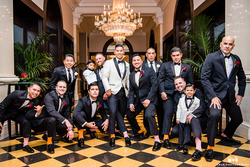 San diego glamorous wedding at the us grant hotel groom white tuxedo with black shawl lapel and black tuxedo pants with a white dress shirt and black bow tie with a white floral boutonniere with groomsmen black tuxedos with black bow ties showing socks