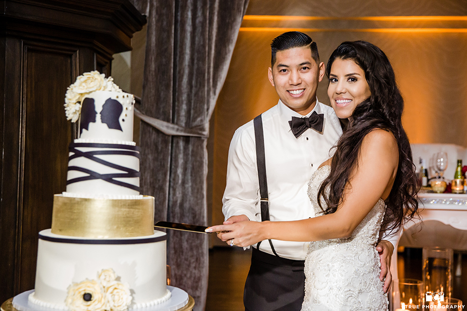 San diego glamorous wedding at the us grant hotel bride strapless ball gown with a tulle skirt and sweetheart neckline and a crystal belt with a long veil and groom white tuxedo jacket with a black shawl and black pants with a black bow tie and white floral boutonniere cutting cake