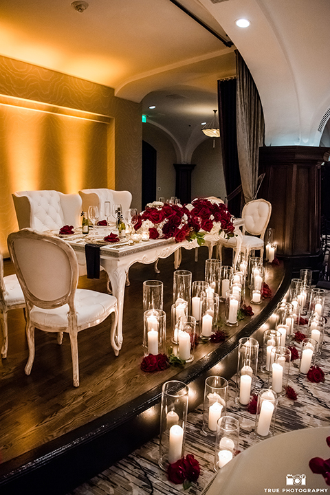 San diego glamorous wedding at the us grant hotel wedding reception decor white vintage sweetheart table and red and white flower centerpiece decor with tall white candles in glass vases on floor wedding photo idea for sweetheart table