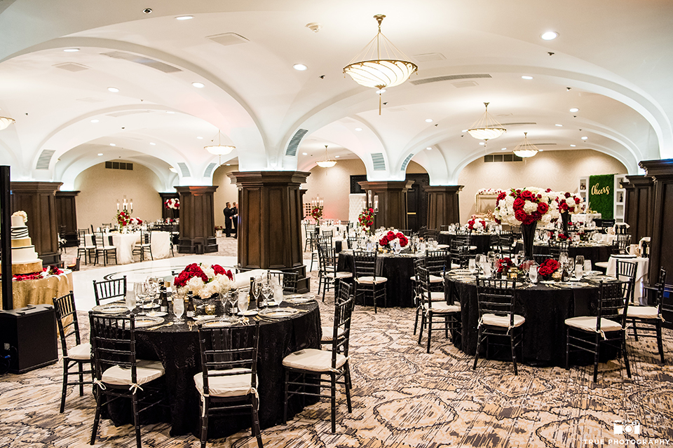 San diego wedding at the us grant hotel wedding reception decor black table linens with black chiavari chairs and white and red flower centerpiece decor with white place settings and gold silverware with candles wedding photo idea for reception table set up