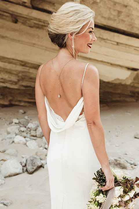 Anza-Borrego-styled-shoot-back-detail-of-bridal-gown-and-jewelry-bride-has-her-hair-up-in-a-bun-with-tear-drop-earrings-oen-back-dress-in-a-bright-bridal-white-with-straps-holding-her-bouquet