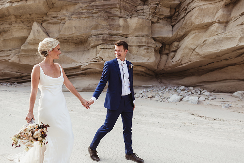 Anza-Borrego-styled-shoot-bride-and-groom-holding-hands-walking-bride-in-white-silk-bridal-gown-with-open-back-and-thin-straps-groom-in-colbalt-blue-suit-with-chocolate-brown-shoes-and-bolo-tie
