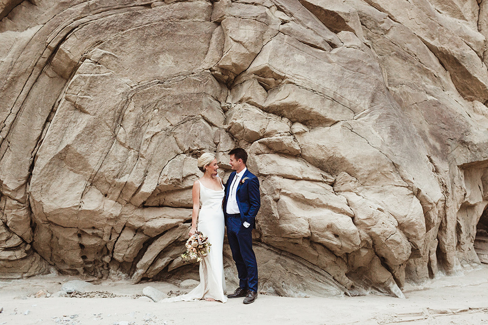 Anza-Borrego-styled-shoot-bride-and-groom-in-front-of-rocks-bride-in-white-silk-bridal-gown-with-open-back-and-thin-straps-groom-in-colbalt-blue-suit-with-chocolate-brown-shoes-and-bolo-tie