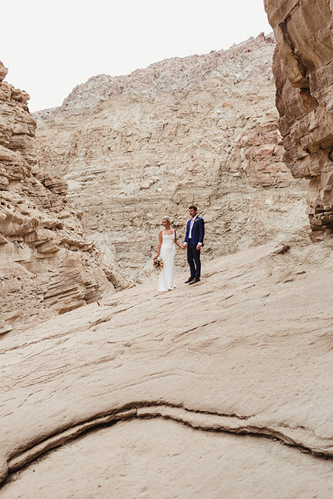 Anza-Borrego-styled-shoot-bride-and-groom-on-slanted-rocks-bride-in-white-silk-bridal-gown-with-open-back-and-thin-straps-groom-in-colbalt-blue-suit-with-chocolate-brown-shoes-and-bolo-tie