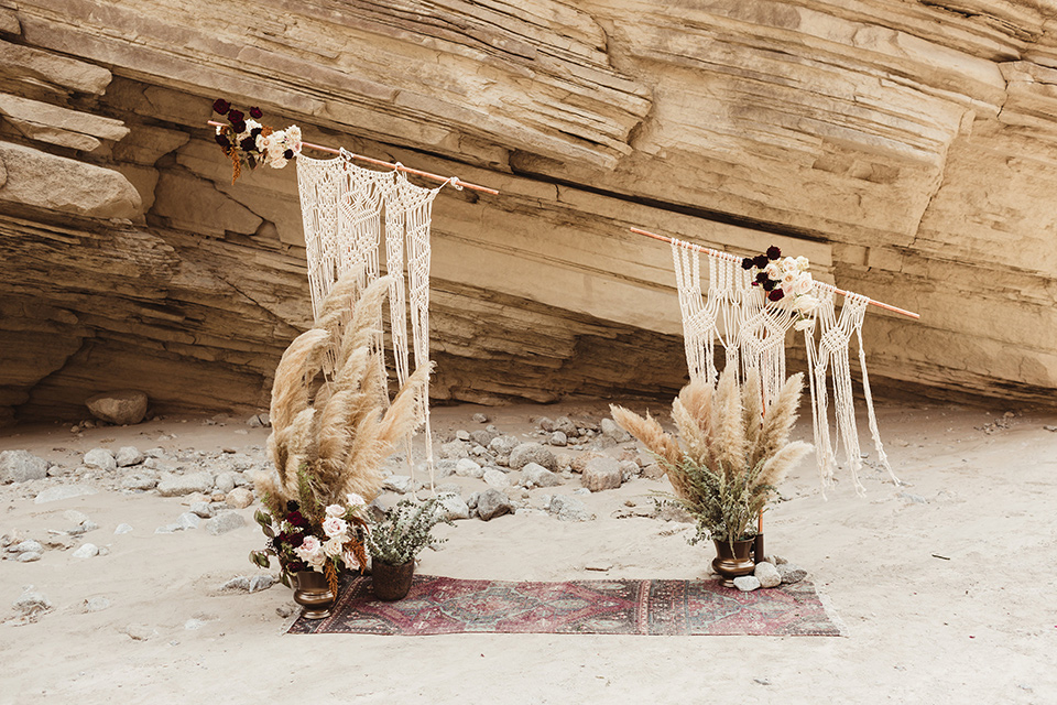 Anza-Borrego-styled-shoot-ceremony-arch-boho-style-with-crochet-drapes-and-florals-on-the-ground