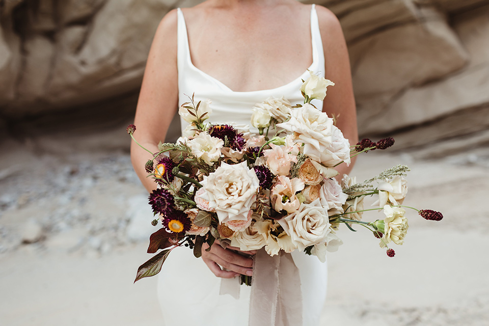 Anza-Borrego-styled-shoot-close-up-on-bridal-bouquet-big-white-flowers-with-small-red-and-green-ones-bride-holding-them-wearing-a-silk-white-gown-with-thin-straps