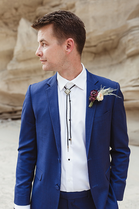Anza-Borrego-styled-shoot-close-up-on-groom-attire-looking-sideways-groom-in-colbalt-blue-suit-with-chocolate-brown-shoes-and-bolo-tie