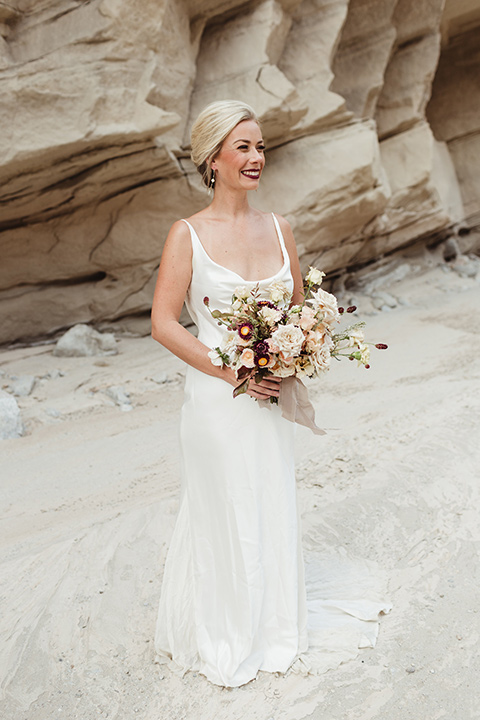Anza-Borrego-styled-shoot-full-length-bridal-gown-look-bride-in-white-silk-bridal-gown-with-open-back-and-thin-straps-and-hair-in-a-sleek-bun-and-dark-red-lipstick
