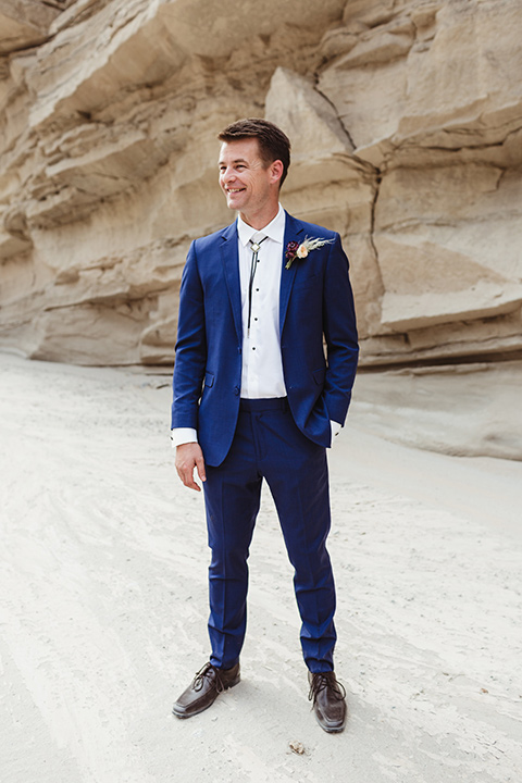 Anza-Borrego-styled-shoot-full-length-groom-attire-groom-in-colbalt-suit-with-chocolate-brown-shoes-and-bolo-tie