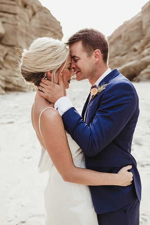 Anza-Borrego-styled-shoot-groom-holding-brides-face-touching-foreheads-bride-in-white-silk-bridal-gown-with-open-back-and-thin-straps-groom-in-colbalt-blue-suit-with-chocolate-brown-shoes-and-bolo-tie