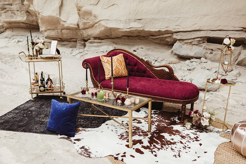 Anza-Borrego-styled-shoot-lounge-chair-and-décor-red-lounge-chair-with-gold-pillows-gold-bar-cart-with-gold-candle-holders-all-around
