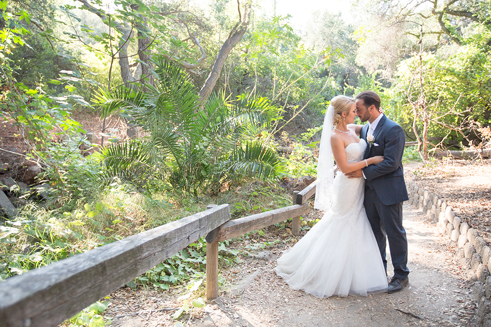 Orange county outdoor wedding at the oak canyon nature center bride form fitting mermaid style strapless gown with a crystal belt and sweetheart neckline with a long veil and groom slate blue notch lapel suit with a matching vest and white dress shirt with a long white tie and white floral boutonniere hugging