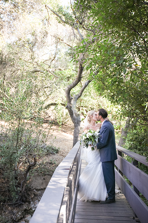 Orange county outdoor wedding at the oak canyon nature center bride form fitting mermaid style strapless gown with a crystal belt and sweetheart neckline with a long veil and groom slate blue notch lapel suit with a matching vest and white dress shirt with a long white tie and white floral boutonniere kissing bride holding white and green floral bridal bouquet