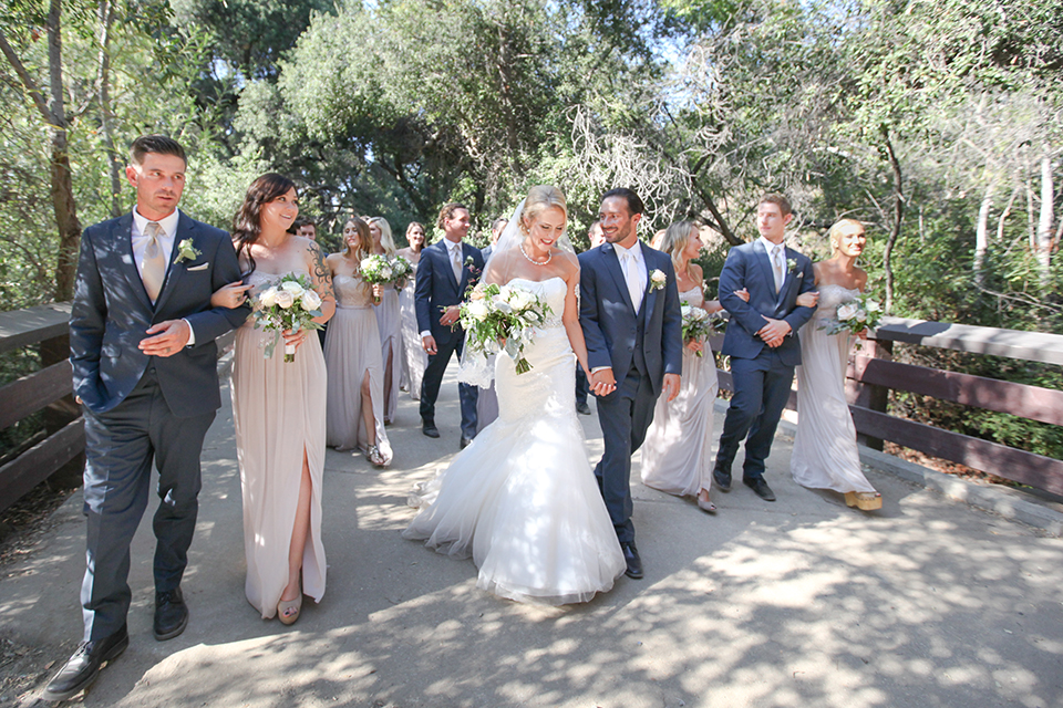 Orange county outdoor wedding at the oak canyon nature center bride form fitting mermaid style strapless gown with a crystal belt and sweetheart neckline with a long veil and groom slate blue notch lapel suit with a matching vest and white dress shirt with a long white tie and white floral boutonniere holding hands and walking with wedding party bridesmaids long grey dresses and groomsmen slate blue suits with long white ties