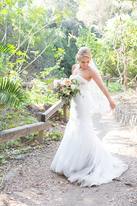 Orange county outdoor wedding at the oak canyon nature center bride form fitting mermaid style strapless gown with a crystal belt and sweetheart neckline with a long veil holding white and green floral bridal bouquet