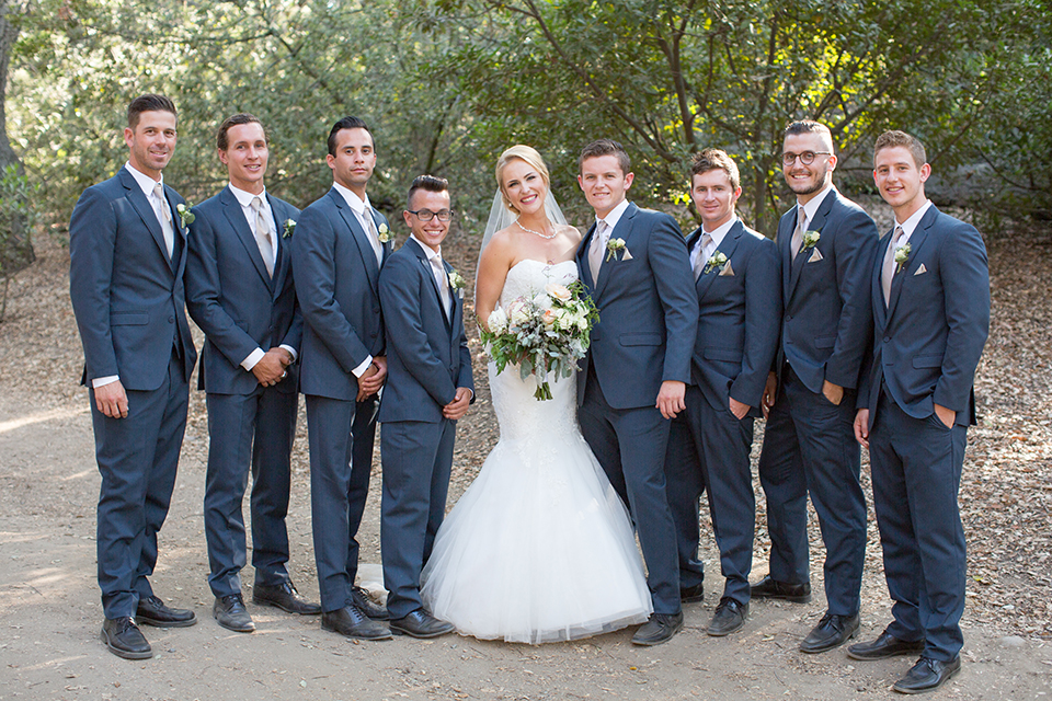 Orange county outdoor wedding at the oak canyon nature center bride form fitting mermaid style strapless gown with a crystal belt and sweetheart neckline with a long veil holding white and green floral bridal bouquet standing with groomsmen slate blue suits with long white ties