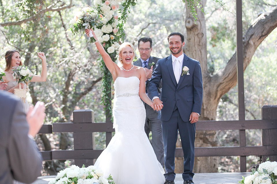Orange county outdoor wedding at the oak canyon nature center bride form fitting mermaid style strapless gown with a crystal belt and sweetheart neckline with a long veil and groom slate blue notch lapel suit with a matching vest and white dress shirt with a long white tie and white floral boutonniere holding hands and cheering after ceremony