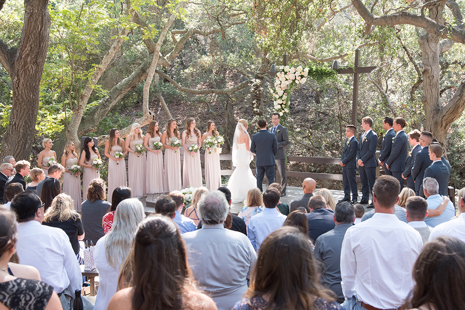 Orange county outdoor wedding at the oak canyon nature center bride form fitting mermaid style strapless gown with a crystal belt and sweetheart neckline with a long veil and groom slate blue notch lapel suit with a matching vest and white dress shirt with a long white tie and white floral boutonniere holding hands during ceremony