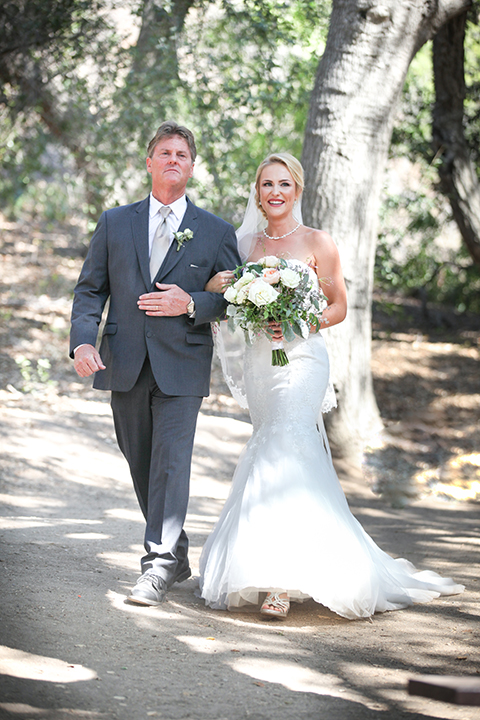 Orange county outdoor wedding at the oak canyon nature center bride form fitting mermaid style strapless gown with a crystal belt and sweetheart neckline with a long veil holding white and green floral bridal bouquet walking down the aisle with dad during ceremony