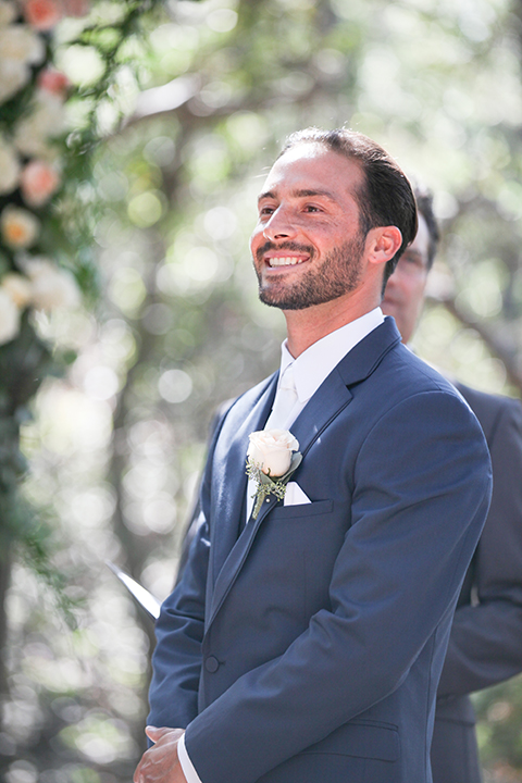 Orange county outdoor wedding at the oak canyon nature center groom slate blue notch lapel suit with a matching vest and white dress shirt with a long white tie and white floral boutonniere watching bride walk down the aisle during ceremony