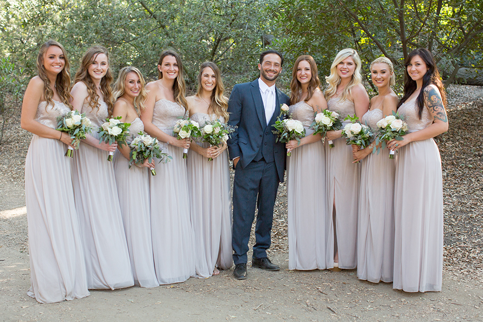 Orange county outdoor wedding at the oak canyon nature center groom slate blue notch lapel suit with a matching vest and white dress shirt with a long white tie and white floral boutonniere standing with bridesmaids long grey dresses holding white and green floral bridal bouquets