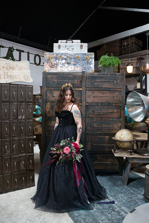 Fox and the owl wedding shoot at big daddys antiques bride black ball gown dress with thin spaghetti straps and a sweetheart neckline holding red floral bridal bouquet