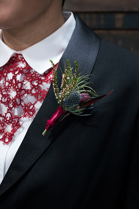 Fox and the owl wedding shot at big daddys antiques bride black womens shawl lapel tuxedo with a white dress shirt and red lace design on neckline with red floral boutonniere