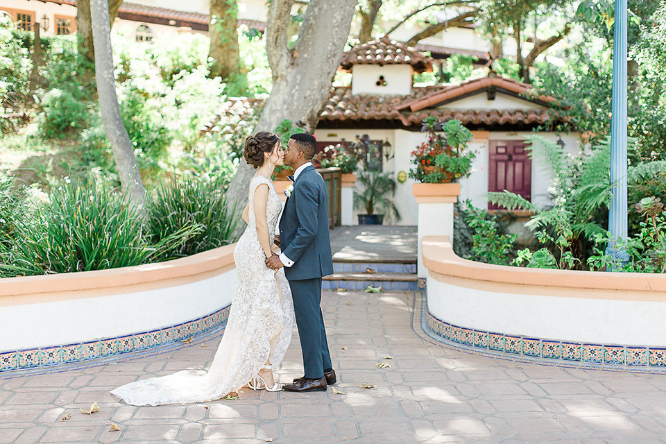 Rancho las lomas outdoor wedding shoot with spanish inspiration bride form fitting lace gown with beaded detail and a plunging neckline with open back design with groom slate blue notch lapel suit with a matching vest and white dress shirt with a matching slate pipe edge bow tie holding hands and kissing