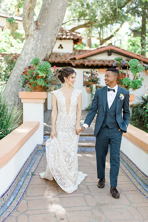Rancho las lomas outdoor wedding shoot with spanish inspiration bride form fitting lace gown with beaded detail and a plunging neckline with open back design with groom slate blue notch lapel suit with a matching vest and white dress shirt with a matching slate pipe edge bow tie holding hands and walking