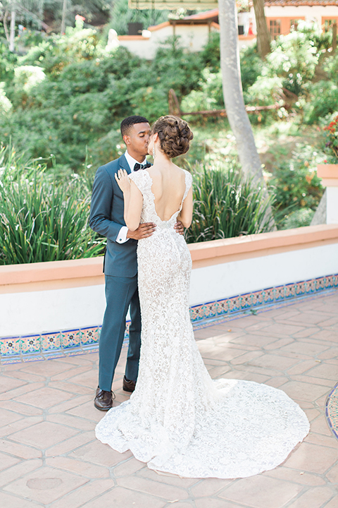 Rancho las lomas outdoor wedding shoot with spanish inspiration bride form fitting lace gown with beaded detail and a plunging neckline with open back design with groom slate blue notch lapel suit with a matching vest and white dress shirt with a matching slate pipe edge bow tie hugging and kissing