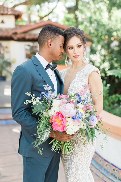 Rancho las lomas outdoor wedding shoot with spanish inspiration bride form fitting lace gown with beaded detail and a plunging neckline with open back design with groom slate blue notch lapel suit with a matching vest and white dress shirt with a matching slate pipe edge bow tie hugging close up and bride holding pink and blue colorful floral bridal bouquet