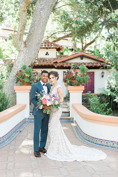Rancho las lomas outdoor wedding shoot with spanish inspiration bride form fitting lace gown with beaded detail and a plunging neckline with open back design with groom slate blue notch lapel suit with a matching vest and white dress shirt with a matching slate pipe edge bow tie standing and hugging bride holding pink and blue floral bridal bouquet