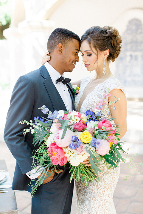 Rancho las lomas outdoor wedding shoot with spanish inspiration bride form fitting lace gown with beaded detail and a plunging neckline with open back design with groom slate blue notch lapel suit with a matching vest and white dress shirt with a matching slate pipe edge bow tie hugging close up and bride holding pink and blue colorful bridal bouquet